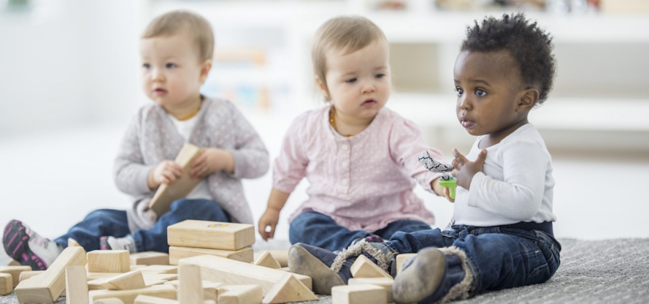 Three babies are sitting on the carpet in a daycare center. They are playing with wooden toy blocks. One girl and boy are arguing over a toy.