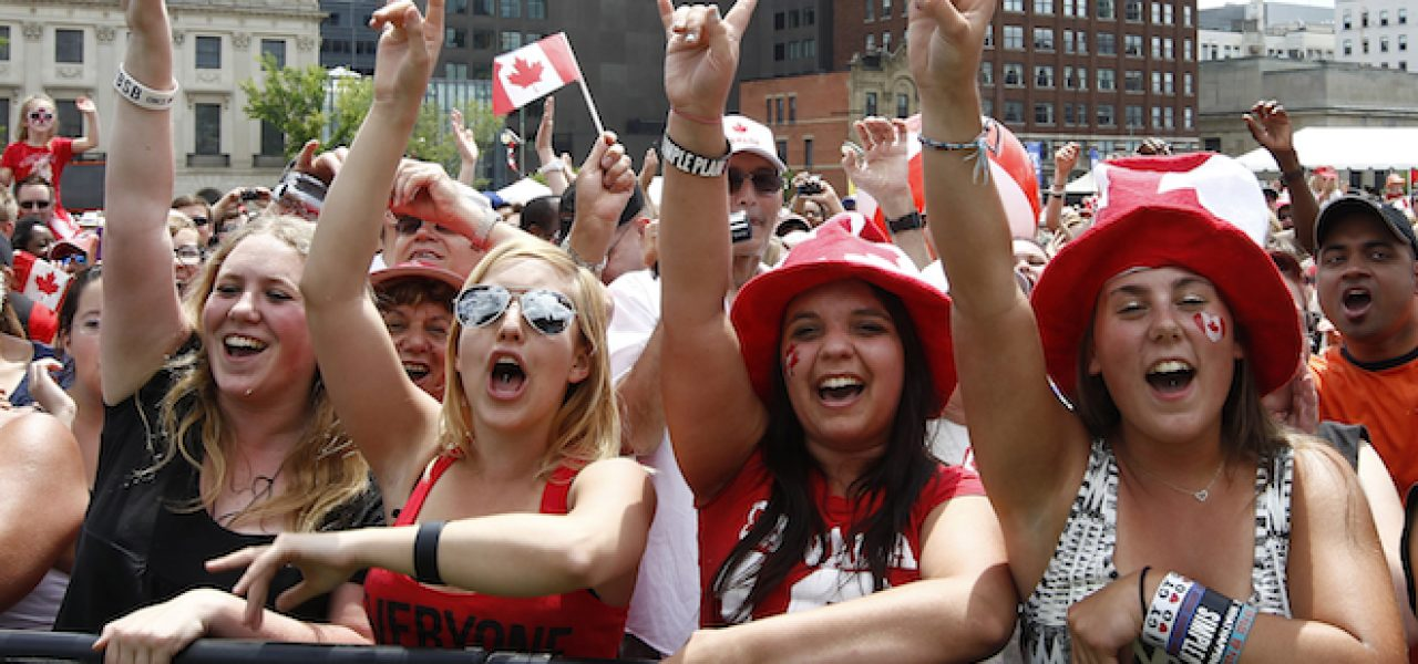 Spectators cheer during Canada Day celebrations on Parliament Hill in Ottawa July 1, 2012. Canadians are celebrating their country's 145th birthday.       REUTERS/Chris Wattie       (CANADA - Tags: POLITICS SOCIETY ANNIVERSARY) - RTR34GEG