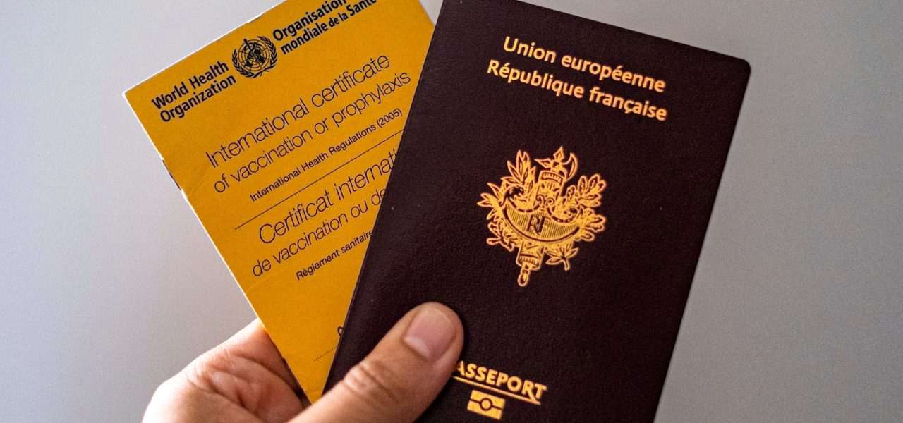In this photo illustration a person's hand holds a vaccination card from the World Health Organisation and a French Passport. (Photo by Walid Berrazeg / SOPA Images/Sipa USA)(Sipa via AP Images) A person holds a World Health Organization vaccination card and a French passport. Walid Berrazeg/SOPA Images/Sipa/AP